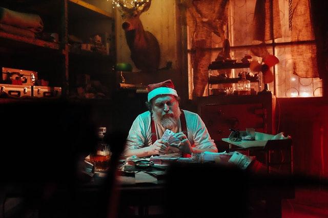 Santa sedí v dílně a přepočítává peníze